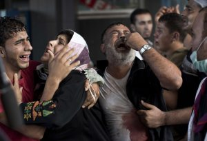 Palestinians crying after seven children were killed by bombs in a refugee camp (Mahmud Hams/ AFP)